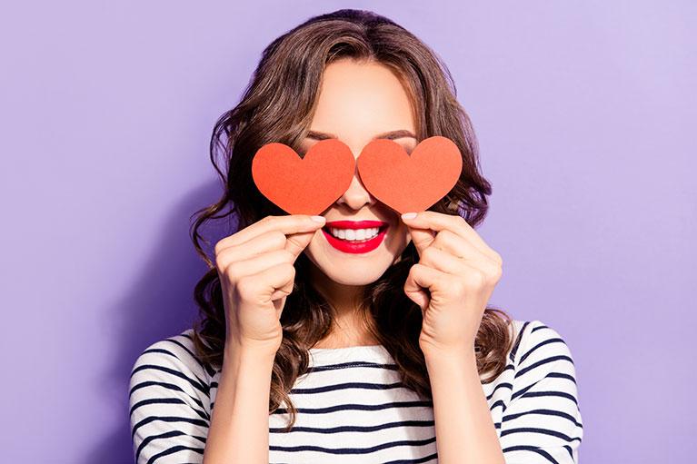 Frau hält sich rote Herzchen vor die Augen: Website vs. Social Media.